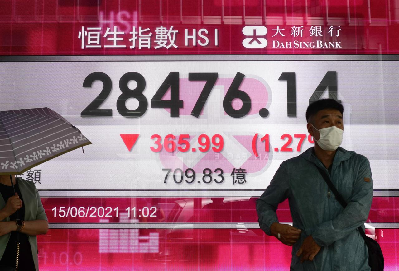 People walk past a bank's electronic board showing the Hong Kong share index at Hong Kong Stock Exchange in Hong Kong Tuesday, June 15, 2021. Shares were mixed in Asia on Tuesday, with Chinese markets losing ground, after gains in several big-name tech companies including Apple helped nudge the S&P 500 to another record high. (AP Photo/Vincent Yu)