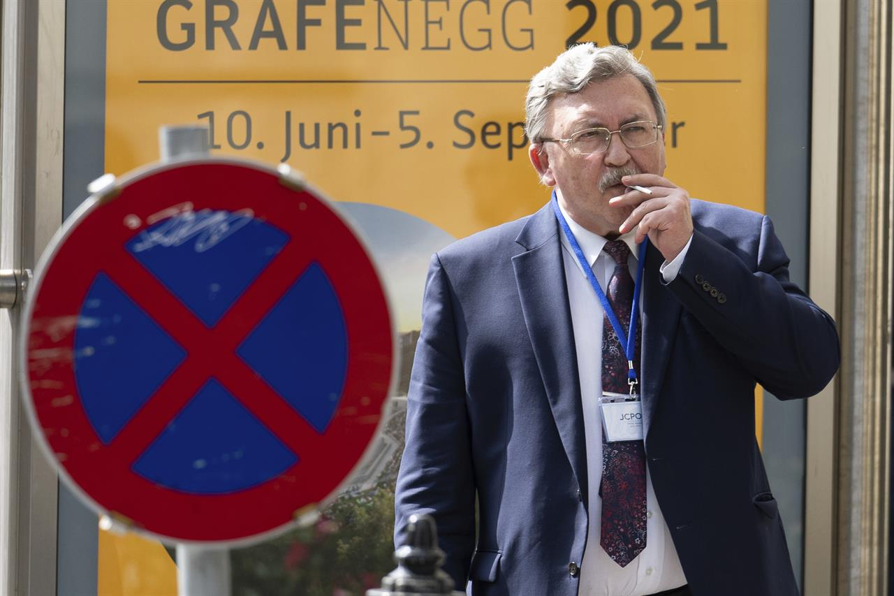 Russia's Governor to the International Atomic Energy Agency (IAEA), Mikhail Ulyanov, smokes a cigarette near the 'Grand Hotel Vienna' where where closed-door nuclear talks take place in Vienna, Austria, Saturday, June 12, 2021. (AP Photo/Florian Schroetter)