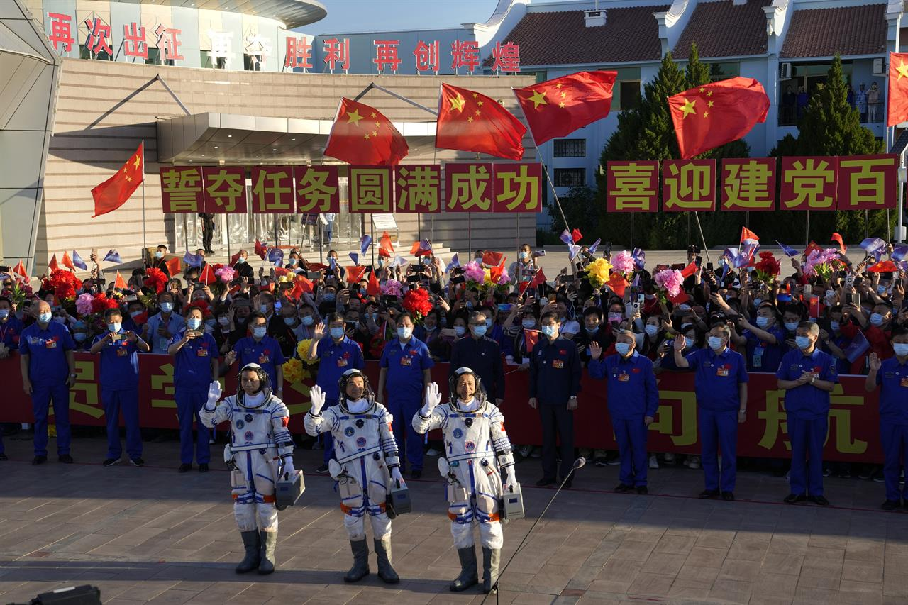 Chinese astronauts, from left, Tang Hongbo, Liu Boming, and Nie Haisheng wave as they prepare to board for liftoff at the Jiuquan Satellite Launch Center in Jiuquan in northwestern China, Thursday, June 17, 2021. China plans on Thursday to launch three astronauts onboard the Shenzhou-12 spaceship who will be the first crew members to live on China's new orbiting space station Tianhe, or Heavenly Harmony. (AP Photo/Ng Han Guan)