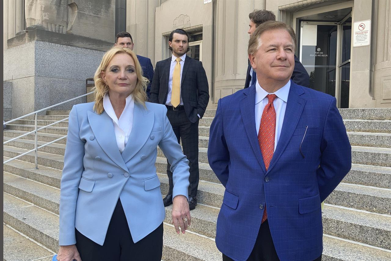 Patricia McCloskey, left, and her husband Mark McCloskey leave a court in St. Louis, Thursday, June 17, 2021. The St. Louis couple who gained notoriety for pointing guns at social justice demonstrators last year has pleaded guilty to misdemeanor charges. Patricia McCloskey pleaded guilty Thursday to misdemeanor harassment and was fined $2,000. Her husband, Mark McCloskey, pleaded guilty to misdemeanor fourth degree assault and was fined $750. The couple also agreed to forfeit both weapons they used when they confronted protesters in front of their home in June of last year. (AP Photo/Jim Salter)
