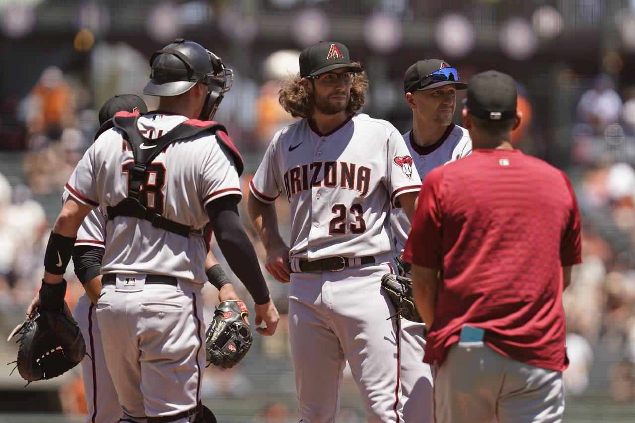 Arizona Diamondbacks starting pitcher Zac Gallen (23) stands on the mound before being removed by manager Torey Lovullo, right, in the third inning of a baseball game against the San Francisco Giants, Thursday, June 17, 2021, in San Francisco. Diamondbacks catcher Carson Kelly, left, and shortstop Nick Ahmed, second from right, look on. (AP Photo/Eric Risberg)