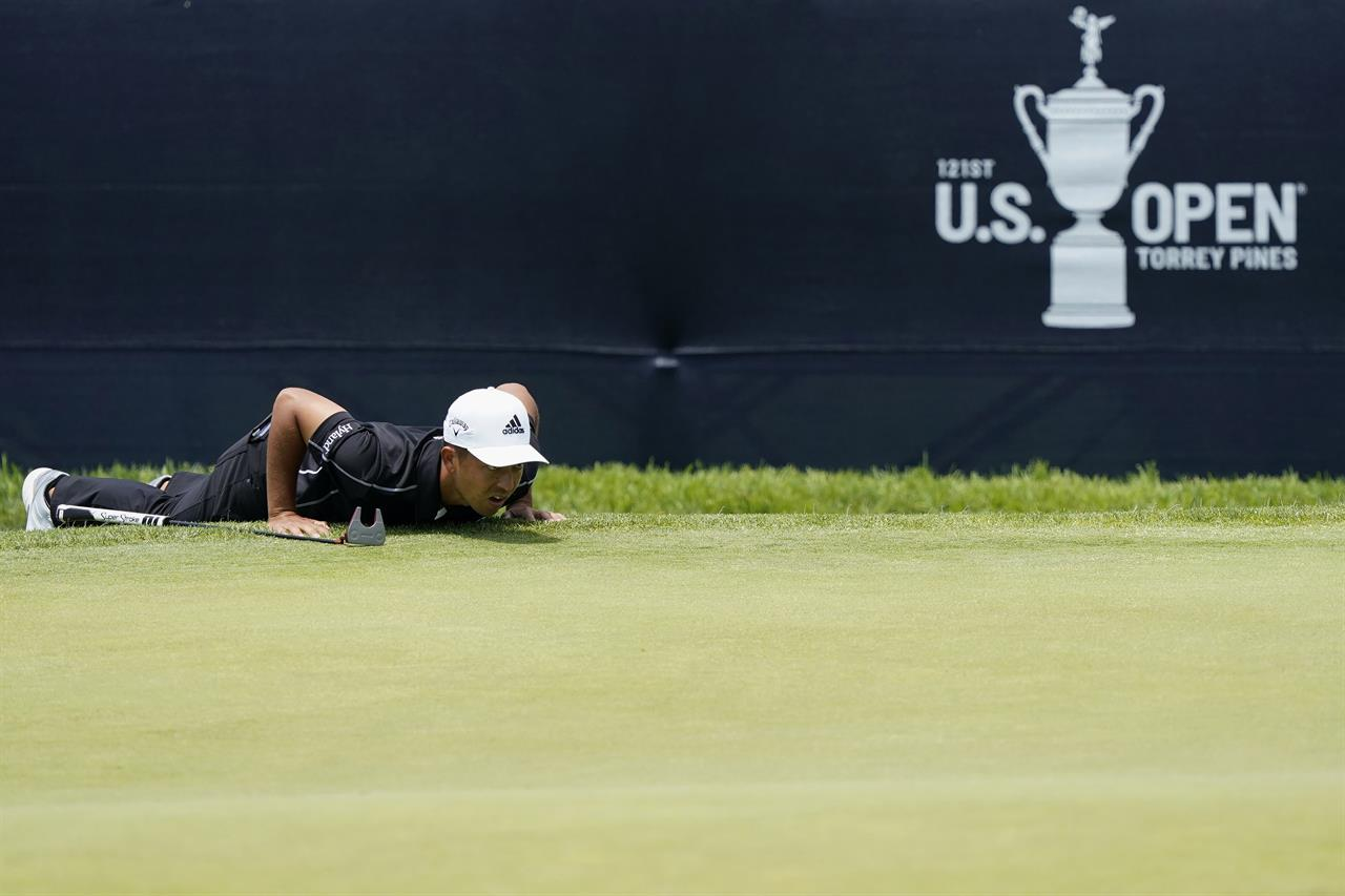 Xander Schauffele reads the lie on the 18th green during the first round of the U.S. Open Golf Championship, Thursday, June 17, 2021, at Torrey Pines Golf Course in San Diego. (AP Photo/Marcio Jose Sanchez)