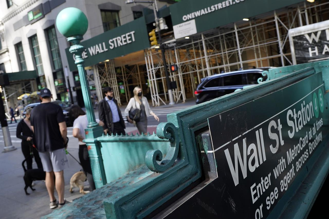 People walk on Broadway at Wall Street, Wednesday, June 16, 2021. Stocks shook off a wobbly start and pushed mostly higher in the first few minutes of trading on Wall Street. The S&P 500 rose 0.1% in the early going Thursday, June 17 and other major indexes were also posting modest gains.  (AP Photo/Richard Drew)