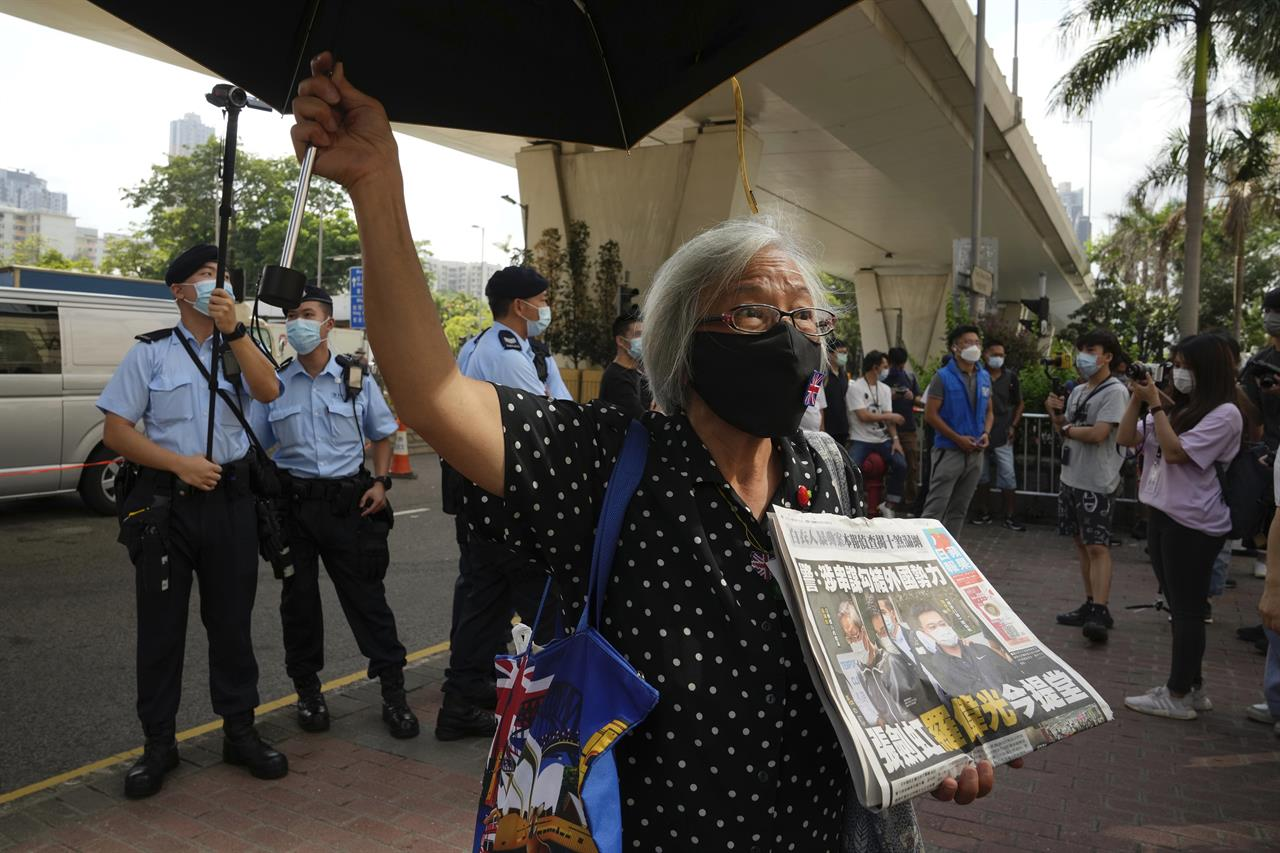 A pro-democracy activist holding a copy of Apple Daily newspaper protests outside a court in Hong Kong, Saturday, June 19, 2021, to demand to release political prisoners. The top editor of the Hong Kong's pro-democracy newspaper and the head of its parent company were brought to a courthouse Saturday for their first hearing since their arrest under the city's national security law.(AP Photo/Kin Cheung)