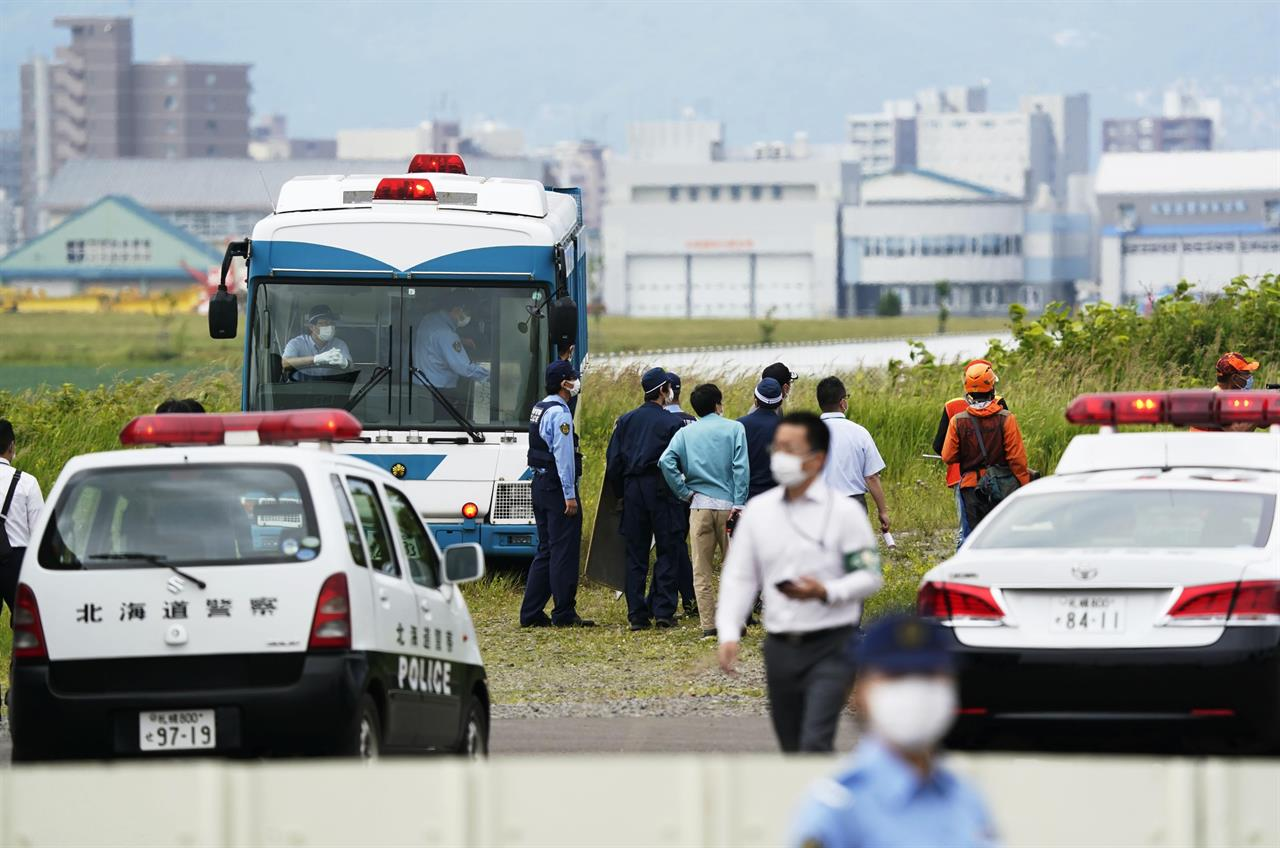 Police gather to look for a bear on the loose in Sapporo, northern Japan Friday, July 18, 2021. A wild brown bear on the loose all night in the city wounded four people, entered a military camp and disrupted flights at the airport Friday before being shot and killed by authorities. (Yohei Fukai/Kyodo News via AP)