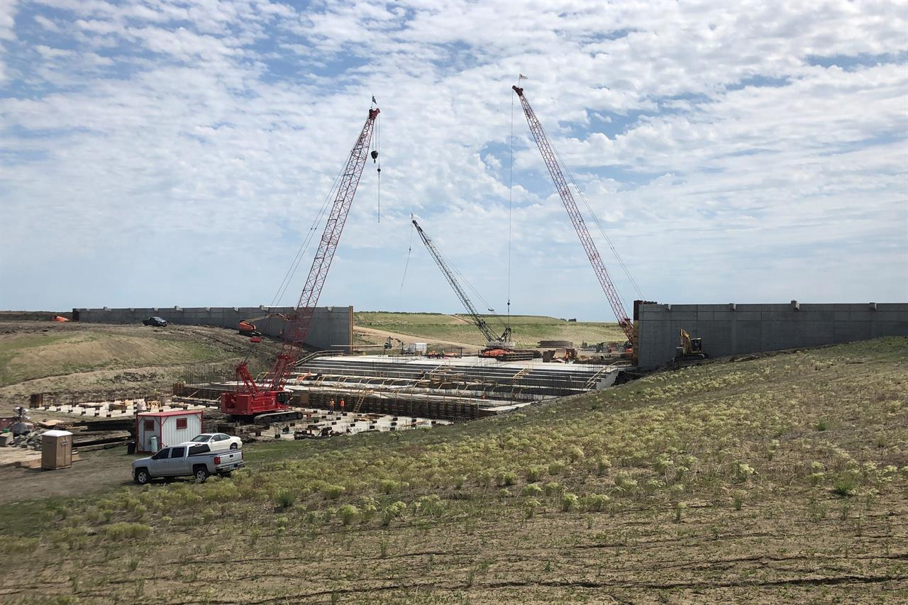 Three cranes are in place to help workers with construction of a water control structure southwest of Fargo, N.D., on Thursday, June 17, 2021. The inlet is part of a 30-mile Red River diversion project that will likely cost $3 billion by the time it's finished in 2027 or 2028. It will be funded by a public-private partnership that officials believe could be a model for big infrastructure projects elsewhere. (AP Photo by David Kolpack)