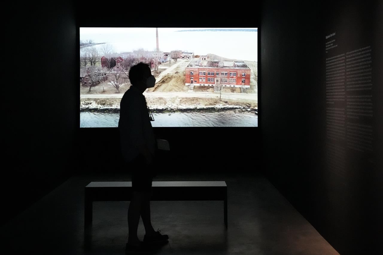 """A man stands in front of the artwork 'Hart Island"""", by Laura Poitras in collaboration with Sean Vegezzi, at an exhibition by American artist and filmmaker Laura Poitras, at the N.K.B. gallery in Berlin, Germany, on Friday, June 18, 2021. The exhibition by Poitras, known for her award-winning 2014 documentary on former U.S. intelligence contractor Edward Snowden, is on display at the gallery until Aug. 8, 2021. (AP Photo/Markus Schreiber)"""