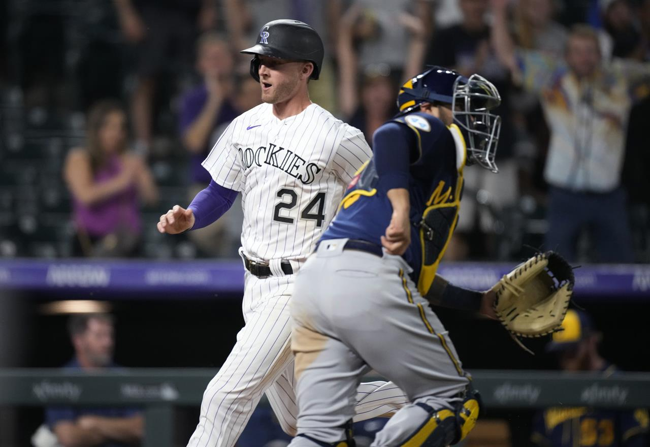 Colorado Rockies' Ryan McMahon, back, crosses home plate to score the winning run as Milwaukee Brewers catcher Omar Narvaez looks for the throw during the 10th inning of a baseball game Friday, June 18, 2021, in Denver. The Rockies won 6-5. (AP Photo/David Zalubowski)