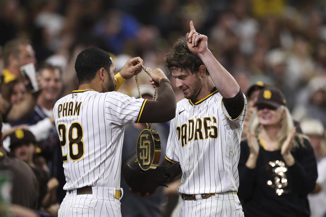 """San Diego Padres' Wil Myers, right, points to the sky as Tommy Pham (28) puts the """"swag chain"""" on him after Myers hit a home run in the fourth inning of the team's baseball game against the Cincinnati Reds Friday, June 18, 2021, in San Diego. (AP Photo/Derrick Tuskan)"""
