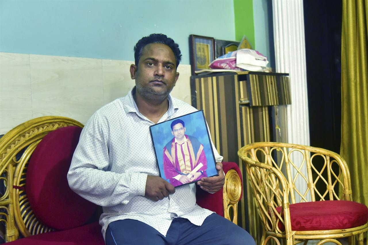 A relative holds a photograph of Dr. Jibraeil, assistant professor of history at Aligarh Muslim Uliversity, who died of COVID-19, in Aligarh, India, Saturday, June 12, 2021. Within just one month, the official Facebook page of Aligarh Muslim University, one of the topmost in India, published about two dozen obituaries of its teachers, all lost to the pandemic. Across the country, the deaths of educators during the devastating surge in April and May have left students and staff members grief-stricken and close-knit university communities shaken.(AP Photo/Manoj Aligadi)