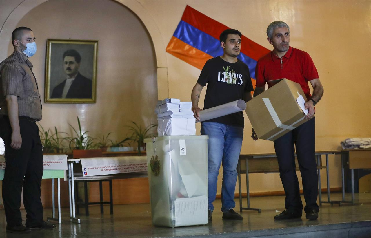 Election officials distribute election attributes to polling stations prior to the upcoming parliamentary elections in Yerevan, Armenia, Saturday, June 19, 2021. Armenians head to the polls Sunday for an early parliamentary election stemming from a political crisis that has engulfed the country in the aftermath of the last year's fighting with Azerbaijan over the separatist region of Nagorno-Karabakh.  (AP Photo/Sergei Grits)