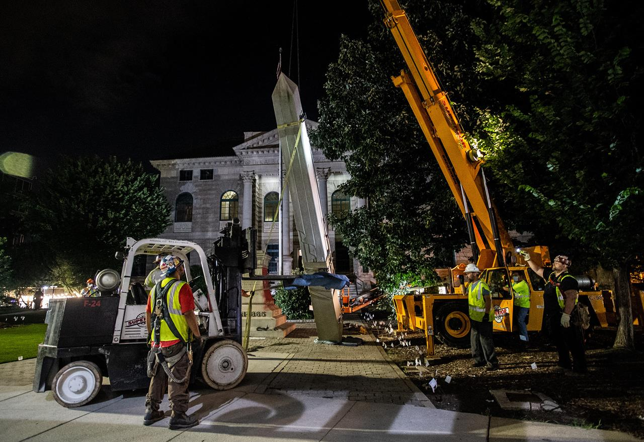 Workers remove a Confederate monument with a crane Thursday, June 18, 2020, in Decatur, Ga. The Sons of Confederate Veterans have sued to return the 30-foot-high obelisk to the site in front of the Georgia courthouse. The monument was taken down last year after a judge in Decatur agreed that it had become a threat to public safety. News outlets report that the suit was filed Wednesday, two days short a year after the monument's removal. (AP Photo/Ron Harris, file)