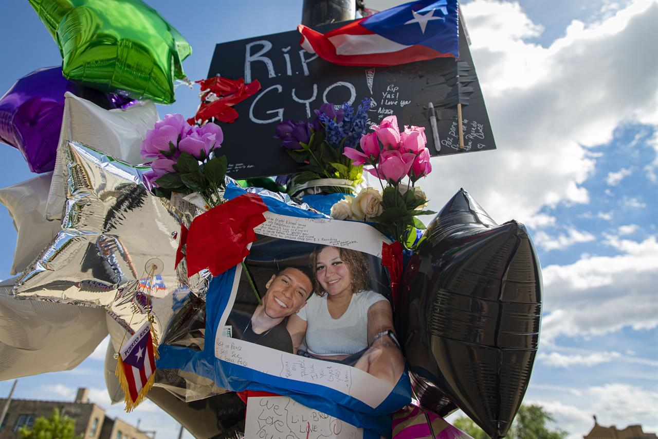 A memorial to shooting victims Gyovanny Arzuaga, 24, and Yasmin Perez, 23, is attached to a pole Tuesday, June 22, 2021 at the corner of West Division Street and North Spaulding Avenue in Humboldt Park in Chicago.  The Cook County medical examiner's office says 23-year-old Yasmin Perez died Tuesday. Her death came three days after 24-year-old Gyovanny Arzuaga was shot in the head and killed following a Puerto Rican Day parade in Chicago's Humboldt Park neighborhood. (Brian Cassella/Chicago Tribune via AP)
