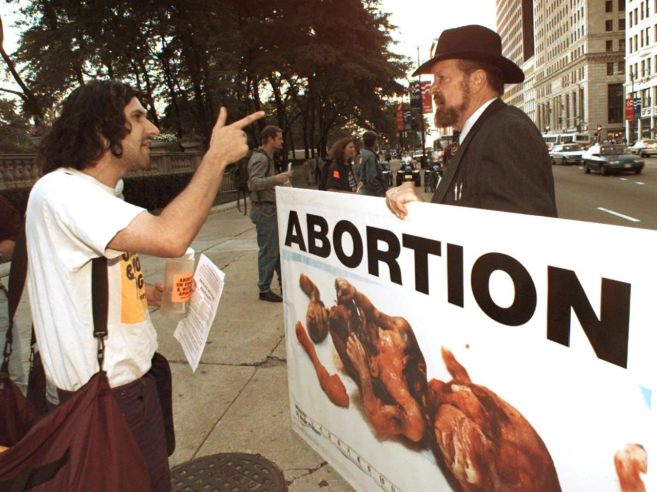 Abortion rights protestor Jay Lynn, left, argues with anti-abortion advocate Joseph Scheidler as he carries a sign along Michigan Ave. in Chicago, Friday, Aug. 23, 1996. Joe Scheidler, the founder of the Pro-Life Action League and prominent figure in the anti-abortion movement, died Monday, Jan. 18, 2021 the organization announced. He was 93. (AP Photo/John Gaps III, file)