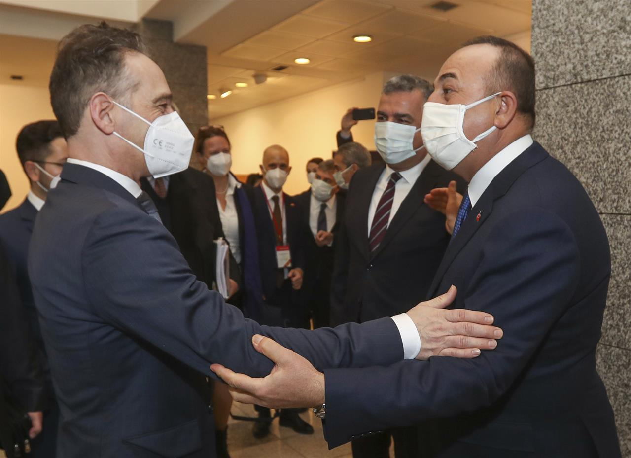 Turkey's Foreign Minister Mevlut Cavusoglu, right greets Germany's Foreign Minister Heiko Maas, left, prior to their meeting, in Ankara, Turkey, Monday, Jan. 18, 2021. (Turkish Foreign Ministry via AP, Pool)