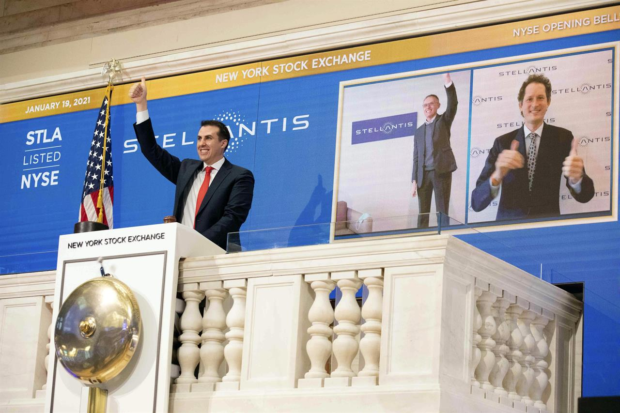 In this photo provided by the New York Stock Exchange, NYSE Vice Chairman John Tuttle, left, Stellantis CEO Carlos Taveras, center, and Chariman John Elkann, right, virtually ring the NYSE opening bell, Tuesday, Jan. 19. 2021. Stellantis shares start trading in New York in the new auto giant created by the merger of Fiat Chrysler and PSA Peugeot. (Colin Ziemer/New York Stock Exchange via AP)