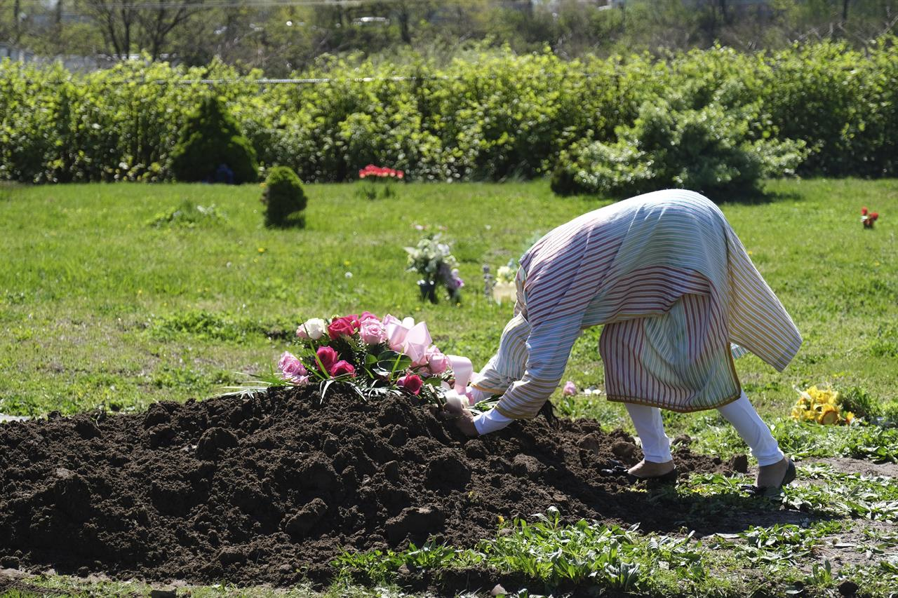 FILE - In this May 2, 2020, file photo, Erika Bermudez becomes emotional as she leans over the grave of her mother, Eudiana Smith, at Bayview Cemetery in Jersey City, N.J., Bermudez was not allowed to approach the gravesite until cemetery workers had buried her mother, who died of COVID-19. Other members of the family and friends stayed in their cars. (AP Photo/Seth Wenig, File)