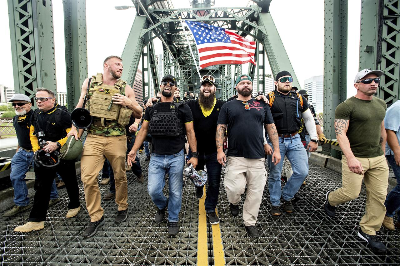 "FILE - Members of the Proud Boys, including organizer Joe Biggs, third from right, march across the Hawthorne Bridge during an ""End Domestic Terrorism"" rally in Portland, Ore., on Saturday, Aug. 17, 2019.  Biggs was arrested Wednesday, Jan. 20, 2021 for taking part in the siege of the U.S. Capitol earlier this month, authorities said. Biggs, 37, was arrested in central Florida and faces charges of obstructing an official proceeding before Congress, entering a restricted on the groups of the U.S. Capitol and disorderly conduct. (AP Photo/Noah Berger, file)"