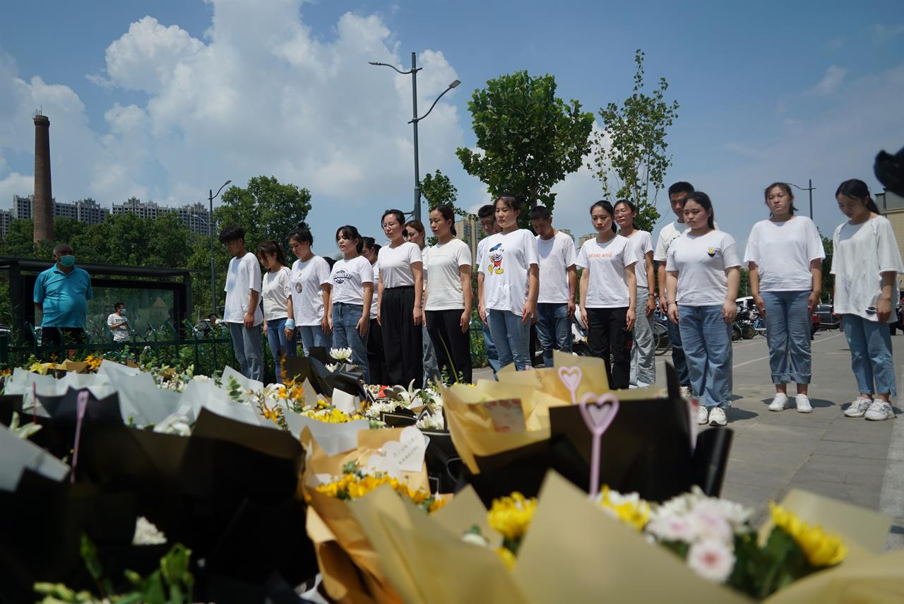 People pay their respects outside the entrance to a subway station in Zhengzhou in central China's Henan Province, Tuesday, July 27, 2021. Residents laid flowers on Tuesday at the entrance of the subway station where more than a dozen people died after a record-breaking downpour flooded large swaths of Henan province in central China. (AP Photo/Dake Kang)