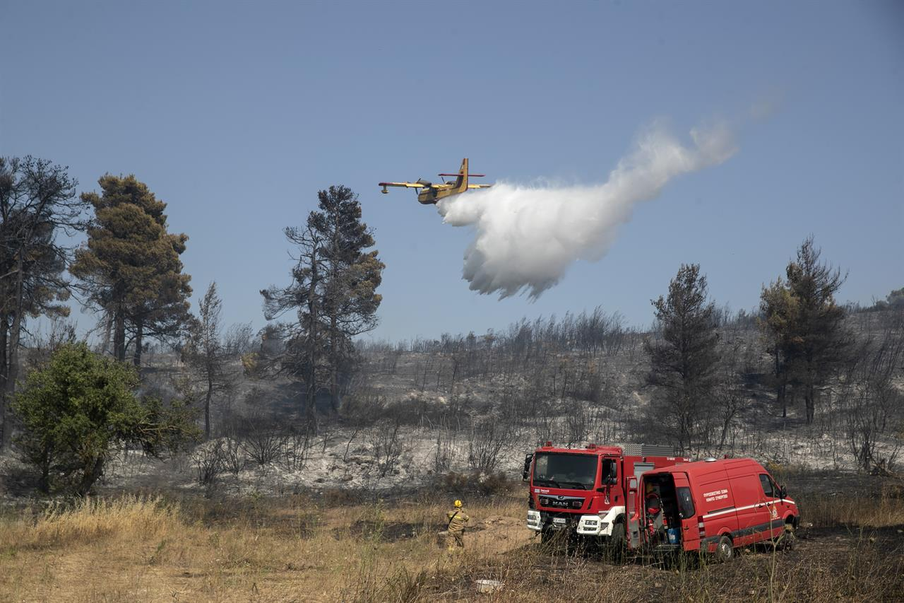 A firefighting airplane drops water during a forest fire at Dionysos northern suburb of Athens, on Tuesday, July 27, 2021. Greek authorities have evacuated several areas north of Athens as a wildfire swept through a hillside forest and threatened homes despite a large operation mounted by firefighters. (AP Photo/Yorgos Karahalis)