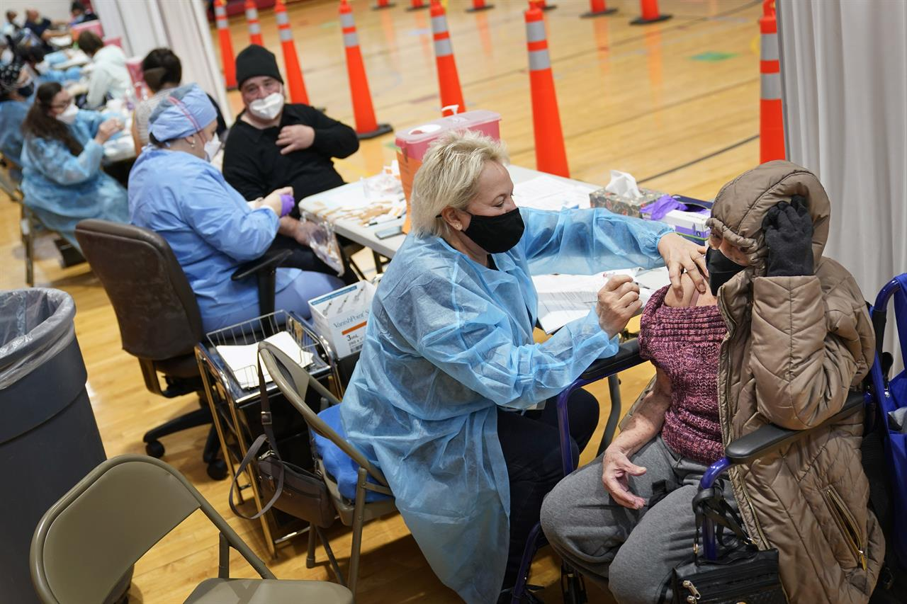 Miriam Palomino, right, received the COVID-19 vaccine in Paterson, N.J., Thursday, Jan. 21, 2021. The first people arrived around 2:30 a.m. for the chance to be vaccinated at one of the few sites that does not require an appointment. (AP Photo/Seth Wenig)
