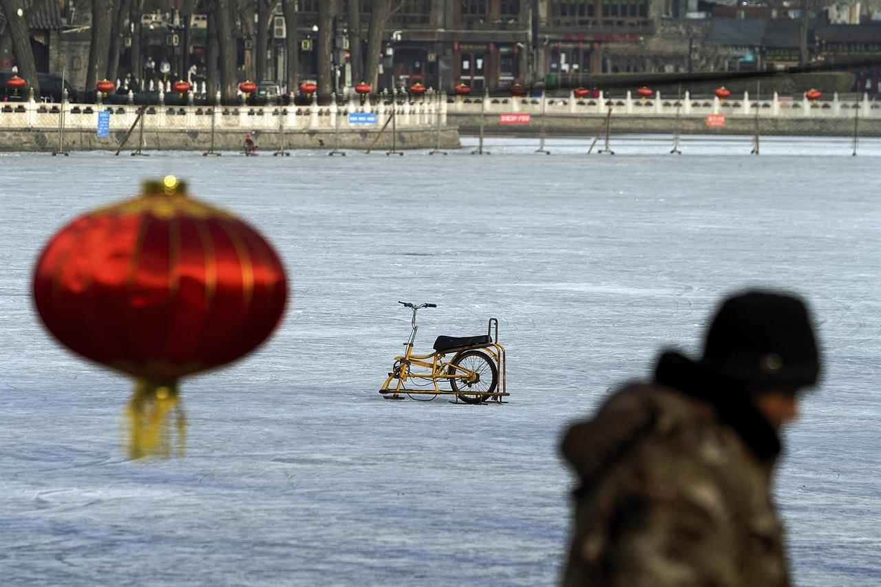 A worker walks by a specially made steel sled parked alone on the capital popular ice skating frozen Houhai Lake after it was ordered to close following the coronavirus cases surge, in Beijing, Thursday, Jan. 21, 2021. China is making some of its toughest travel restrictions yet as coronavirus cases surge in several northern provinces ahead of the travel rush for Lunar New Year next month. (AP Photo/Andy Wong)