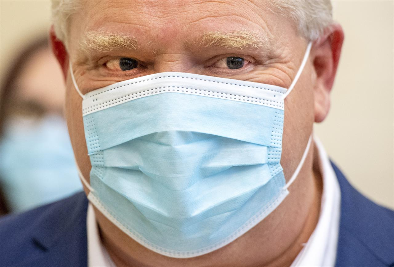 Ontario Premier Doug Ford looks on as a dose of the Pfizer-BioNTech COVID-19 vaccine is administered at The Michener Institute in Toronto on Monday, Jan. 4, 2021. (Frank Gunn/The Canadian Press via AP)