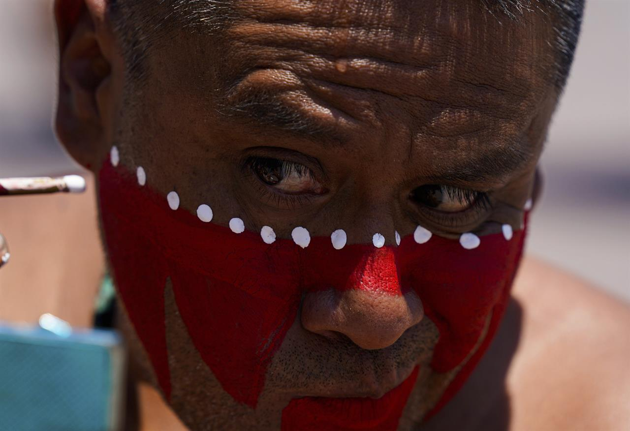 A dancer applies makeup prior to a performance as part of the commemoration marking the 700th founding anniversary of the Aztec city Tenochtitlan, known today as Mexico City, at the main square Zocalo, in Mexico City, Monday, July 26, 2021, amid the new coronavirus pandemic. (AP Photo/Fernando Llano)