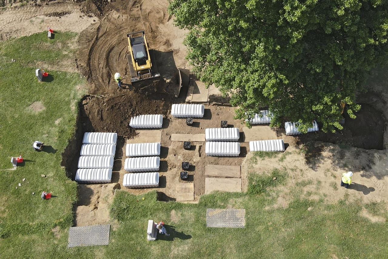 In this aerial photo, a mass grave is re-filled with dirt after a small ceremony at Oaklawn Cemetery, Friday, July 30, 2021, in Tulsa, Okla. The mass grave was discovered while searching for victims of the Tulsa Race Massacre. (Mike Simons/Tulsa World via AP)