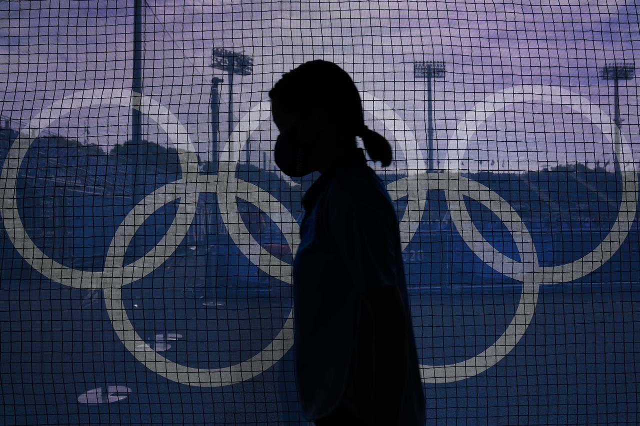 A field attendant passes netting emblazoned with the Olympic rings on the north pitch of Oi Hockey Stadium before a women's field hockey match between Argentina and Germany at the 2020 Summer Olympics, Monday, Aug. 2, 2021, in Tokyo, Japan. (AP Photo/John Locher)