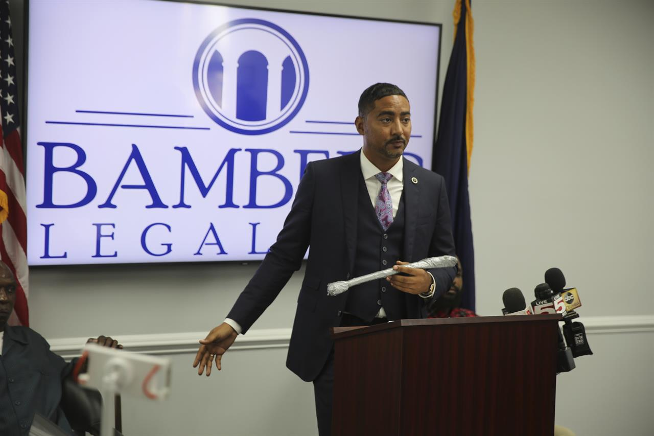 Attorney Justin Bamberg holds up a stick that he said a 911 called mistook for a gun that led to an officer stomping his client in the neck during Bamberg's news conference on Tuesday, Aug. 3, 2021 in Orangeburg, South Carolina. Orangeburg Public Safety officer David Lance Dukes was fired and charged with a felony after the July 26 incident. (AP Photo/Jeffrey Collins)
