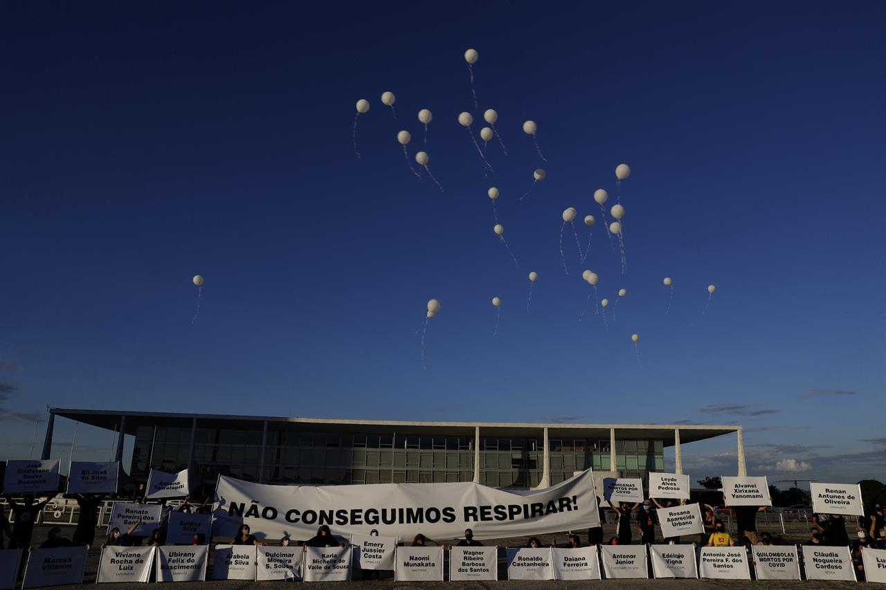"""Demonstrators open a large banner with text written in Portuguese that reads """"We can't breathe"""" while releasing white balloons representing the more than 200,000 deaths caused by the COVID-19 pandemic, during a protest against the lack of action to combat the new Coronavirus by the administration of Brazil's President Jair Bolsonaro, in front of the presidential palace, in Brasilia, Brazil, Thursday, Jan. 21, 2021. (AP Photo/Eraldo Peres)"""