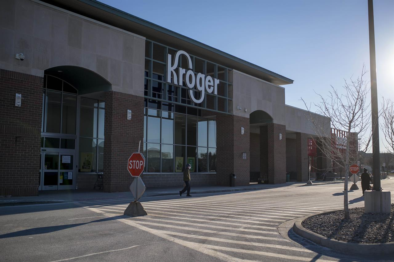 A person walks across the street outside of the Kroger  in Novi, Mich on Jan. 23, 2021. A $1 billion winning Mega Millions ticket was sold at the store for the drawing held on Friday, Jan. 22.  (Nic Antaya/Detroit News via AP)
