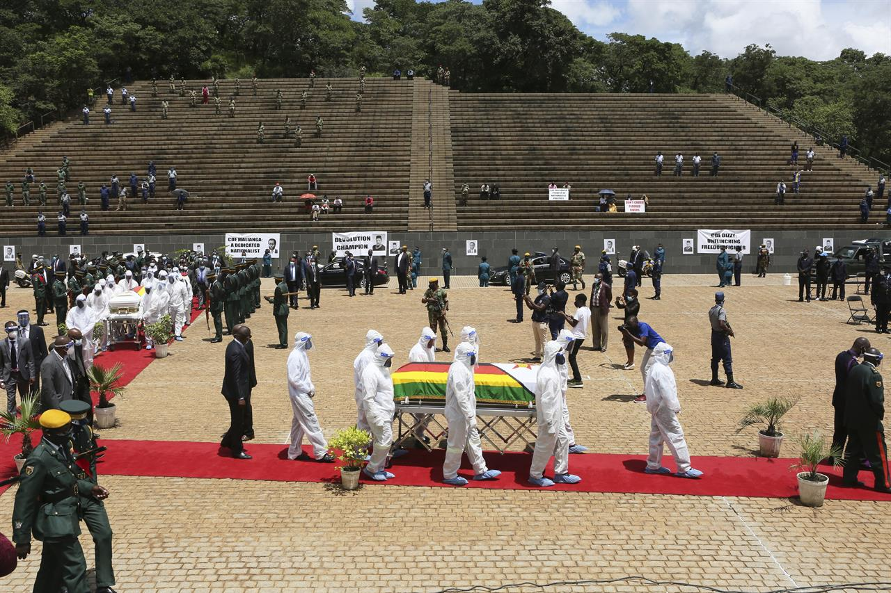 """Pallbearers carry the coffin of a government minister of Dr Ellen Gwaradzimba who died of COVID-19, at the Heroes Acre in Harare, Thursday, Jan. 21, 2021. Zimbabwean President Emmerson Mnangagwa who presided over the burial called the pandemic """"evil"""" and urged people to wear masks, practice social distancing and sanitize, as cases across the country increased amid a fragile health system. (AP Photo/Tsvangirayi Mukwazhi)"""