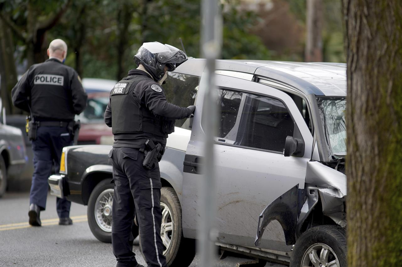 Police investigate after a driver struck and injured at least five people over a 20-block stretch of Southeast Portland, Ore., before crashing and fleeing on Monday, Jan. 25, 2021, according to witnesses. (Beth Nakamura/The Oregonian via AP)