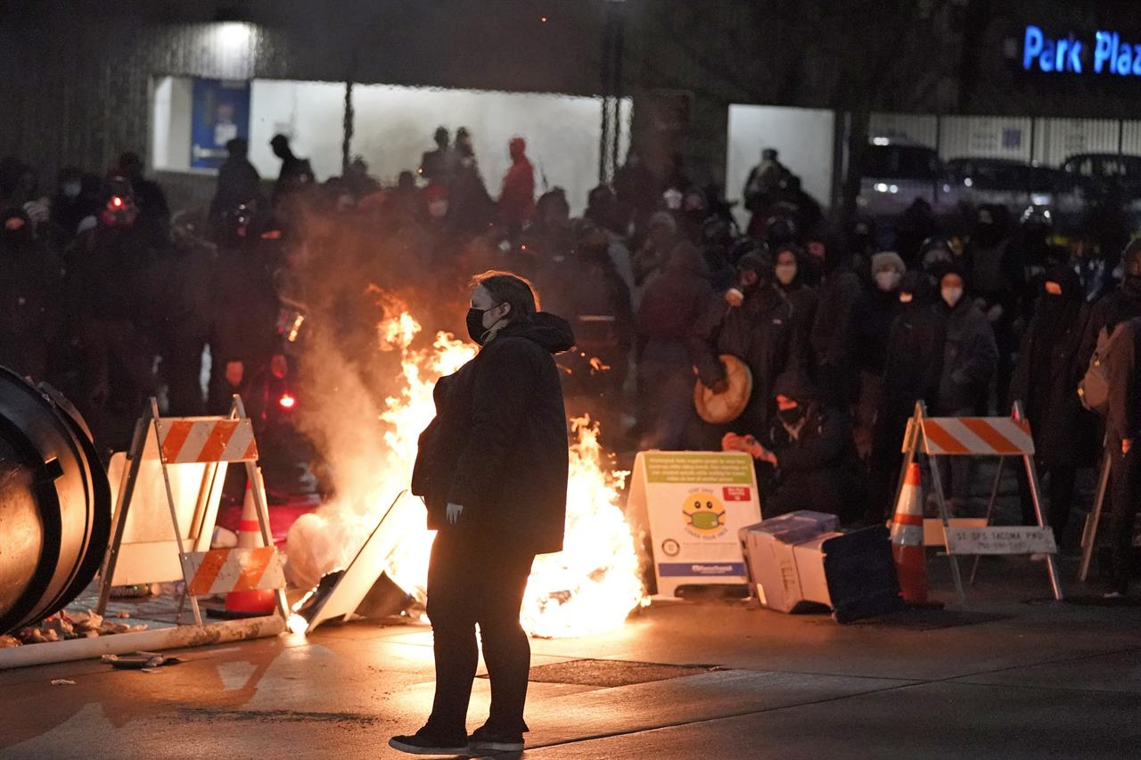 A protester walks past burning trash during a protest against police brutality, late Sunday, Jan. 24, 2021, in downtown Tacoma, Wash., south of Seattle. The protest came a day after at least two people were injured when a Tacoma Police officer responding to a report of a street race drove his car through a crowd of pedestrians that had gathered around him. Several people were knocked to the ground and at least one person was run over. (AP Photo/Ted S. Warren)