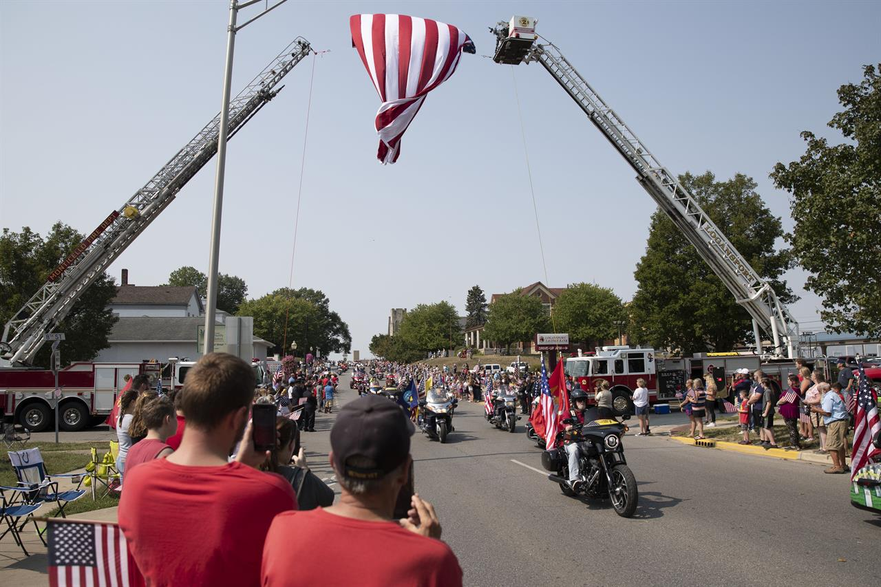 Thousands of people on motorcycles drive past the crowd during the funeral procession for Marine Corps Cpl. Humberto Sanchez  on Sunday, Sept. 12, 2021, in Logansport, Ind. Sanchez was among 13 U.S. service members killed in a suicide bombing during the U.S.-run evacuation at Afghanistan's Kabul airport on Aug. 26. (Christine Tannous /The Indianapolis Star via AP)