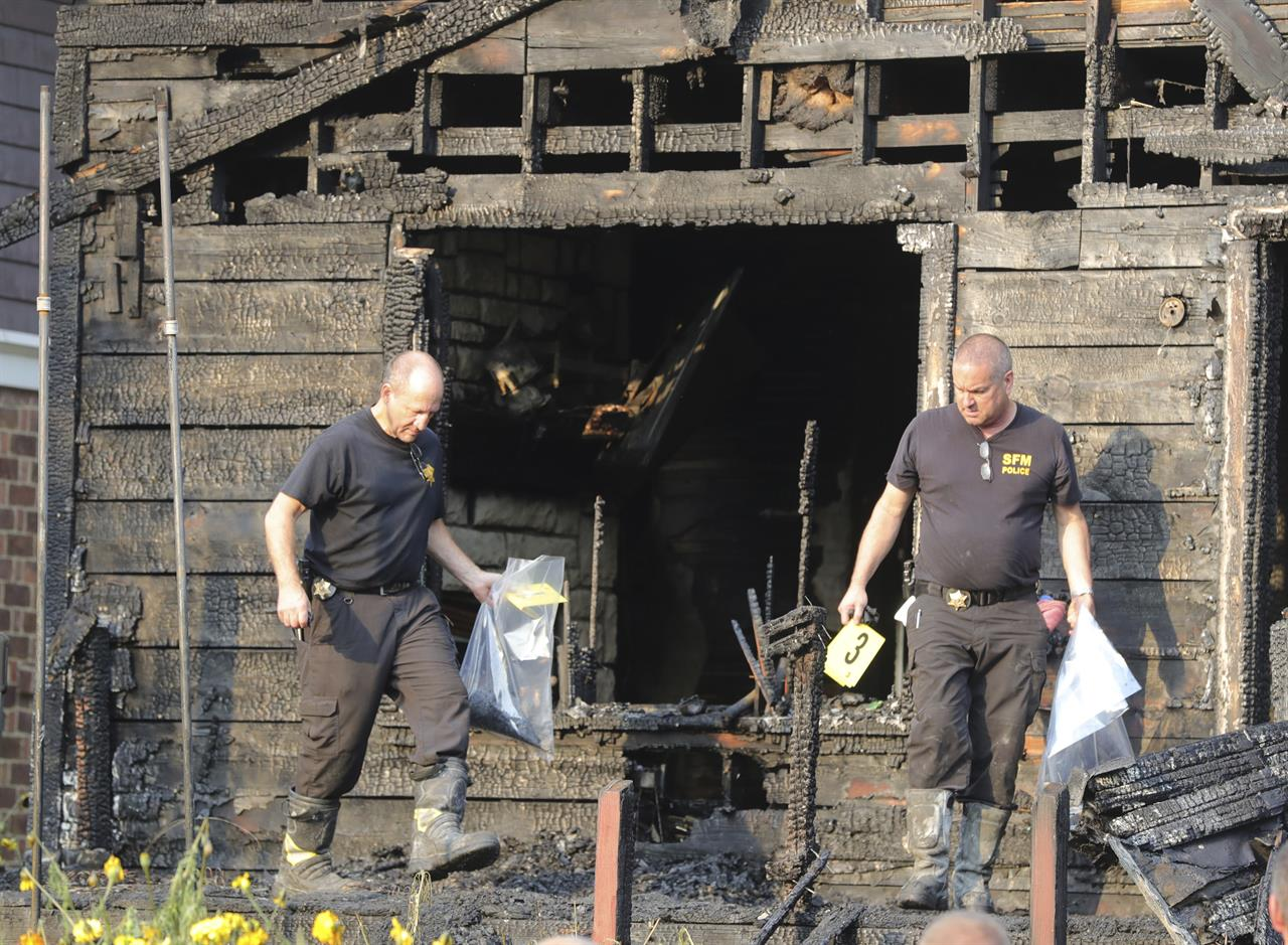 Inspectors from the state fire marshal's  office gather evidence at the scene of a fatal fire on Monday, Sept. 13, 2021 in Akron, Ohio. Authorities say five people are dead and four are injured in a house fire in northern Ohio. The Summit County Medical Examiner's Office says two adults and three children were killed. (Phil Masturzo/ Beacon Journal via AP)