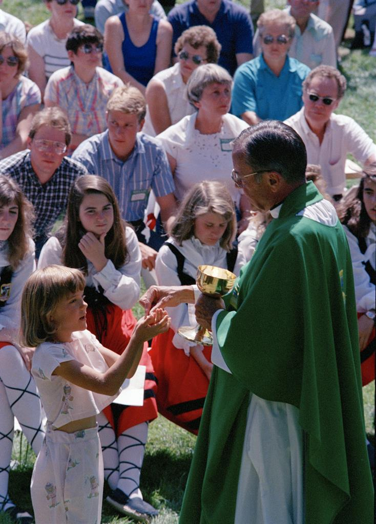 """FILE - In this Spet. 19, 1988 file photo Rev. Joseph Hart dispenses communion during an outdoor Mass celebrated for participants of the Basque Festival in Buffalo, Wyo. On Tuesday, Jan. 26, 2020 the Vatican's Congregation for the Doctrine of the Faith cleared retired Cheyenne, Wyoming Bishop Hart of seven accusations of abuse, determined that five others couldn't be proven """"with moral certitude"""" and that two cases involving boys, who were 16 and 17, couldn't be prosecuted given the Catholic Church didn't consider them minors at the time of the alleged abuse, the diocese said. (AP Photo/Dean Wariner, File)"""