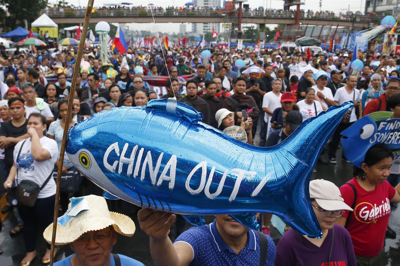 FILE - In this July 22, 2019, file photo, protesters display a balloon with an anti-China message during a rally near the Philippine Congress in Manila, Philippines. The Philippines has protested a new Chinese law that authorizes its coast guard to fire on foreign vessels and destroy other countries' structures on islands it claims, Manila's top diplomat said Wednesday, Jan. 27, 2021.  (AP Photo/Bullit Marquez, File)