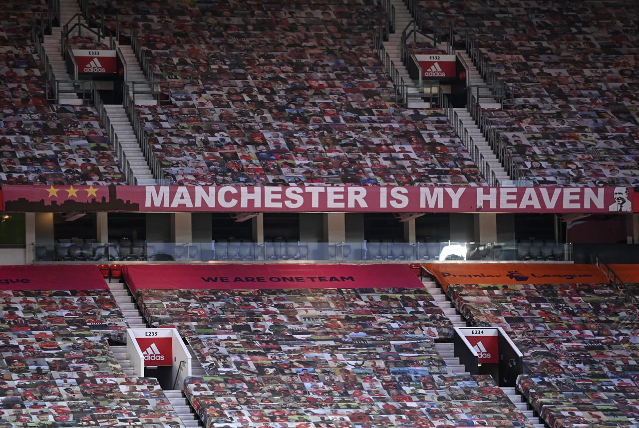 Empty stands are covered with photos of supporters ahead of the English FA Cup 4th round soccer match between Manchester United and Liverpool at Old Trafford in Manchester, England, Sunday, Jan. 24, 2021. (Laurence Griffiths/Pool via AP)
