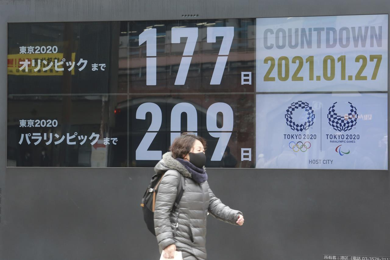 A woman walks past a countdown clock for Tokyo Olympic and Paralympic Games in Tokyo, Wednesday, Jan. 27, 2021. (AP Photo/Koji Sasahara)