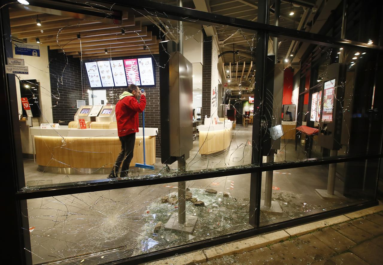 A man cleans up broken glass from the smashed windows in a fast-food restaurant that was damaged in protests against a nation-wide curfew in Rotterdam, Netherlands, Monday, Jan. 25, 2021. The Netherlands Saturday entered its toughest phase of anti-coronavirus restrictions to date, imposing a nationwide night-time curfew from 9 p.m. until 4:30 a.m. in a bid to control the COVID-19 infection rate. (AP Photo/Peter Dejong)