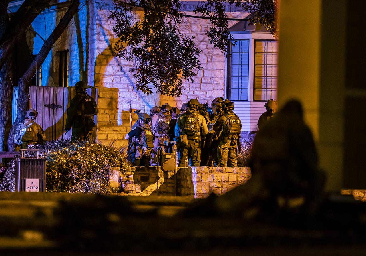Police begin to enter a building as they respond to hostage situation at doctor's office in Austin, Texas, where, police said, two people were found dead after police entered the building Tuesday, Jan. 26, 2021. After several hours of trying to reach the people inside the building, the Austin Police Department had a robot unit go in and identified a victim, officials said. (Ricardo B. Brazziell/Austin American-Statesman via AP)