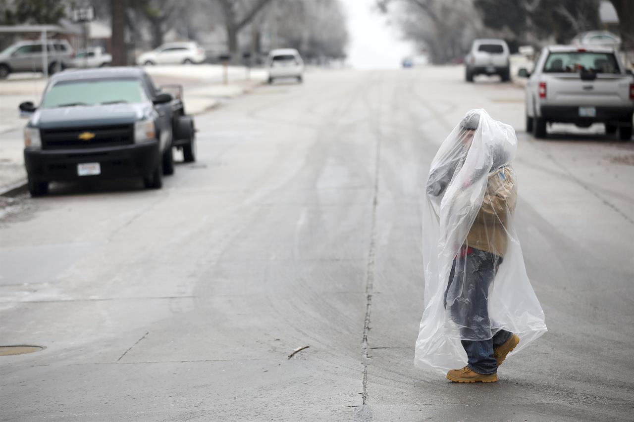 James Andrews uses a plastic bag to stay warm and dry while he walks on Delaware Ave. north of I-244 Wednesday, Feb. 10, 2021 in Tulsa, Okla. (Mike Simons/Tulsa World via AP)