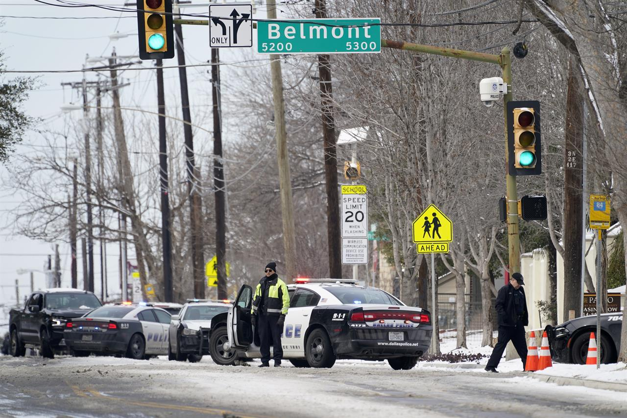 A Dallas police presence is seen at the street intersection of Belmont and Henderson in a neighborhood where earlier in the day two other officers were shot responding to an emergency call in Dallas, Thursday, Feb. 18, 2021. (AP Photo/Tony Gutierrez)