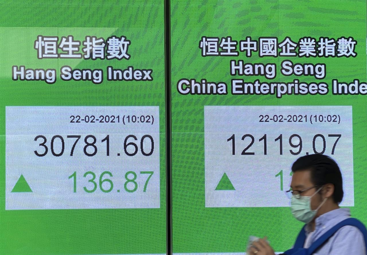 A man walks past a bank's electronic board showing the Hong Kong share index in Hong Kong Monday, Feb. 22, 2021. Asian shares were mixed on Monday as hopes for a recovery from the coronavirus pandemic with the global rollout of vaccines were countered by worries about inflation and continuing economic damage.  (AP Photo/Vincent Yu)