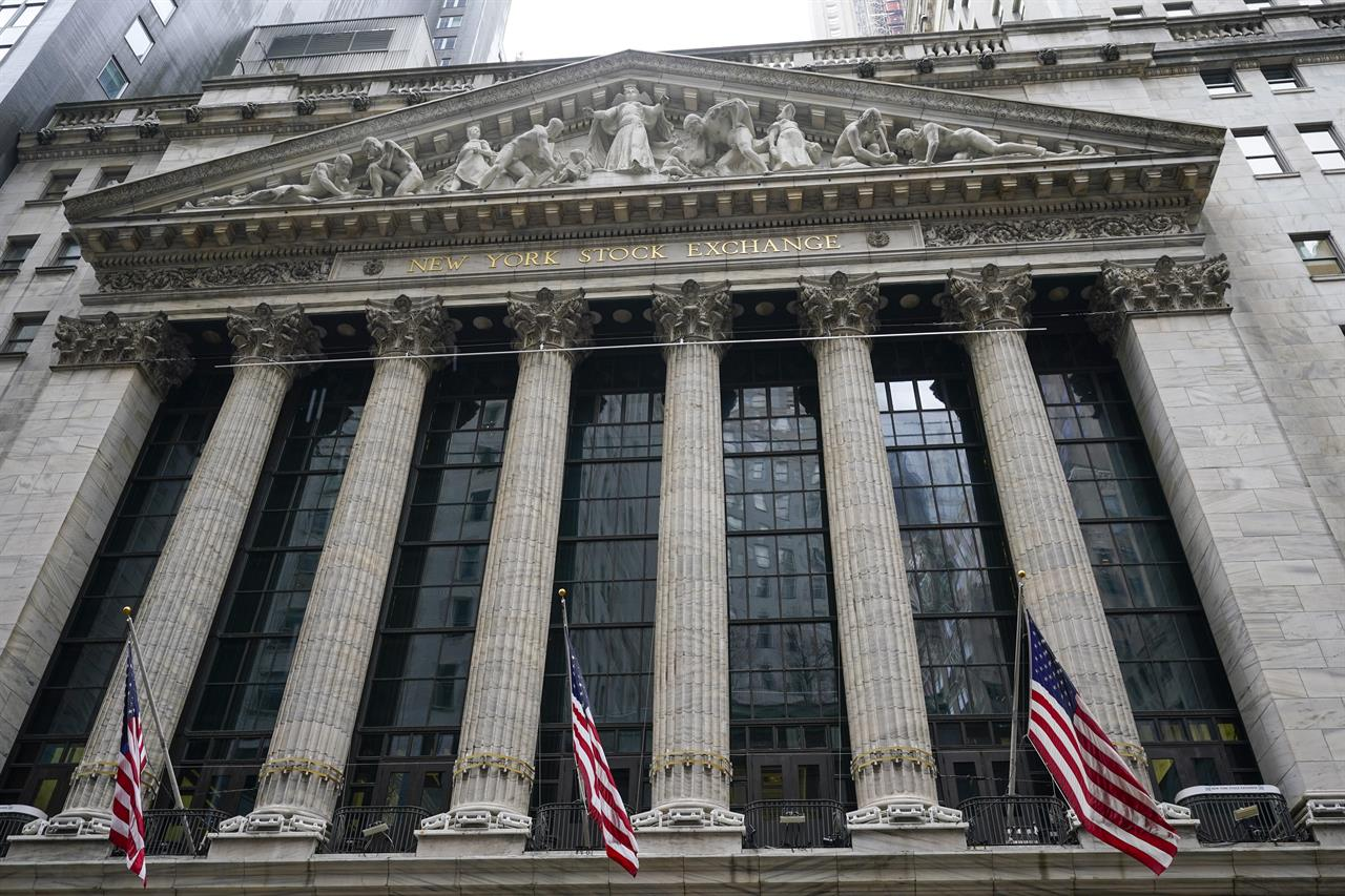 FILE - In this Tuesday, Feb. 16, 2021, American flags hang outside of the New York Stock Exchange in New York. Stocks are opening broadly lower on Wall Street, getting the week off to a sluggish start and continuing a losing streak. The S&P 500 gave up 0.6% in the early going Monday, Feb. 22 and other major indexes were also lower.   (AP Photo/Frank Franklin II, File)