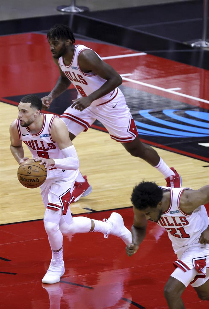 Chicago Bulls'  Zach LaVine, left, heads upcourt with the ball during the third quarter of an NBA basketball game against the houston RocketsMonday, Feb. 22, 2021, in Houston. (Carmen Mandato/Pool Photo via AP)