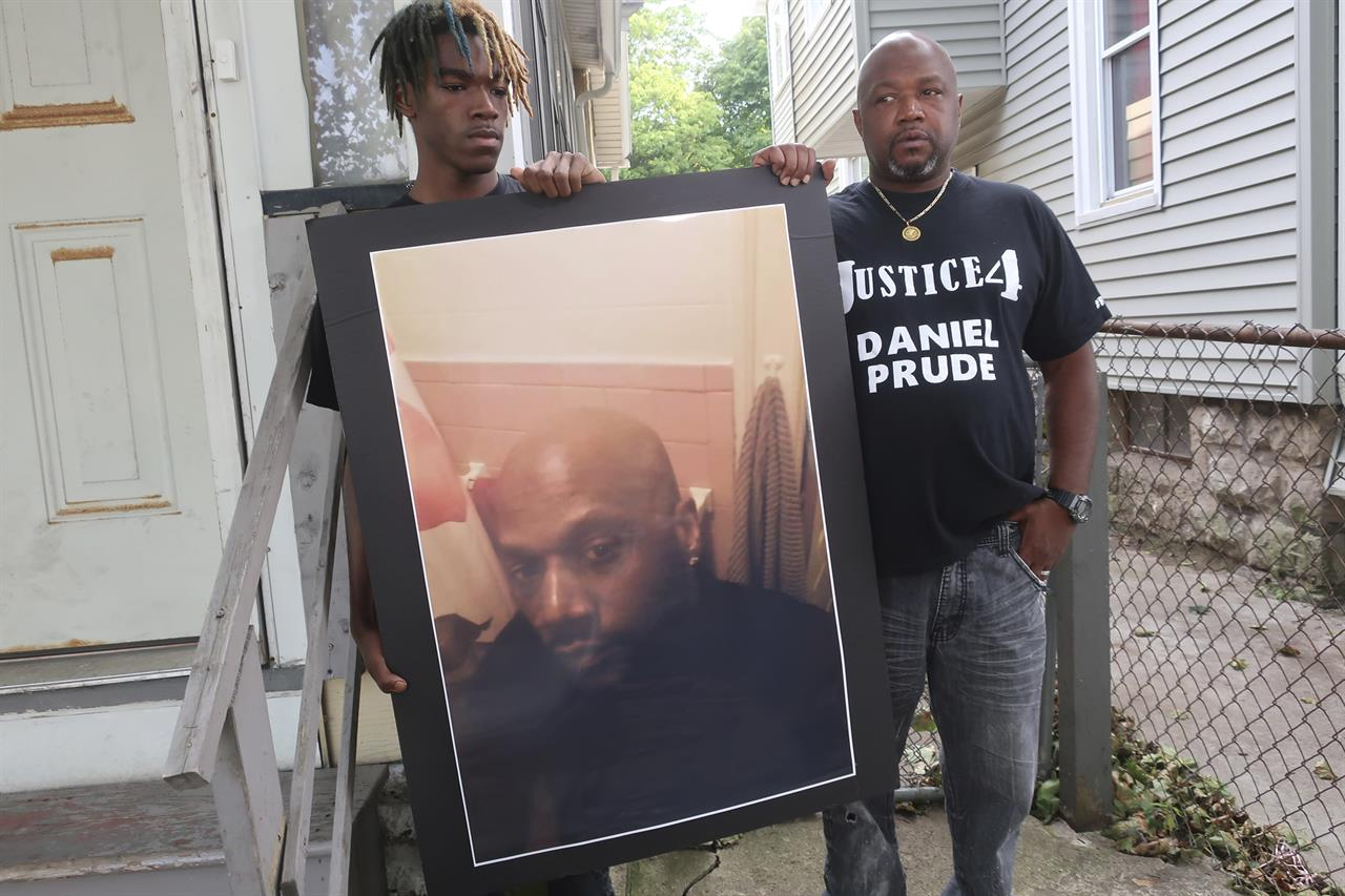 "FILE - In this Sept. 3, 2020, file photo, Joe Prude, brother of Daniel Prude, right, and his son Armin, stand with a picture of Daniel Prude in Rochester, N.Y. Daniel Prude, 41, suffocated after police in Rochester put a ""spit hood"" over his head while he was being taken into custody. He died March 30, after he was taken off life support, seven days after the encounter with police. The independent investigator leading a probe of the city's handling of Prude's death says the ex-police chief is refusing to cooperate. (AP Photo/Ted Shaffre, File)"